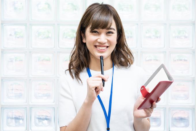手帳を見てスケジュール確認をしている女性