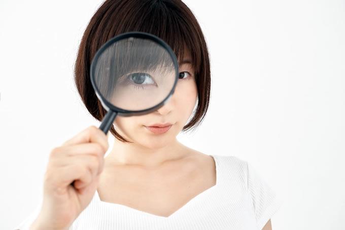 虫眼鏡を見ている女性