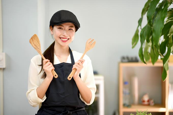 調理器具を持つ笑顔の女性