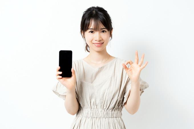 スマートフォンを持ってOKサインをしている女性