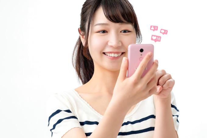 スマートフォンでSNSを確認している女性