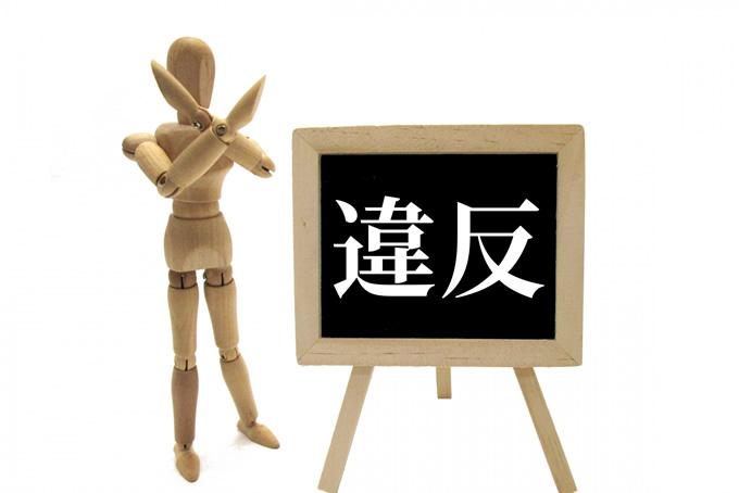 バツサインをする人形と違反ボード