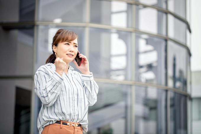 困った顔で電話をする女性