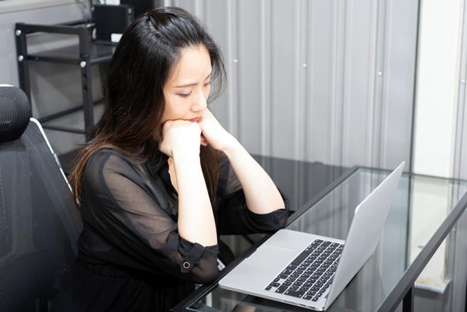 パソコンを見て落ち込む女性