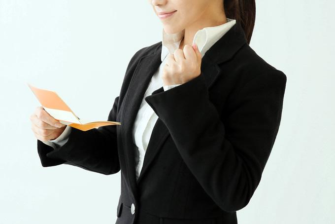 通帳を見てガッツポーズをする女性