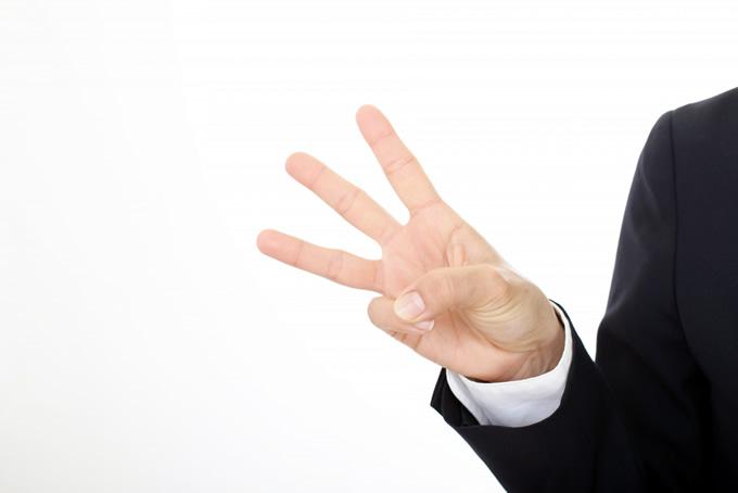指で3を示す男性