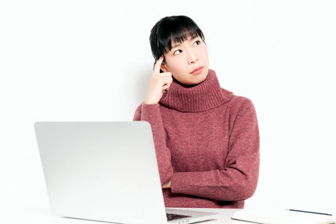 パソコンの前で悩んでいる女性