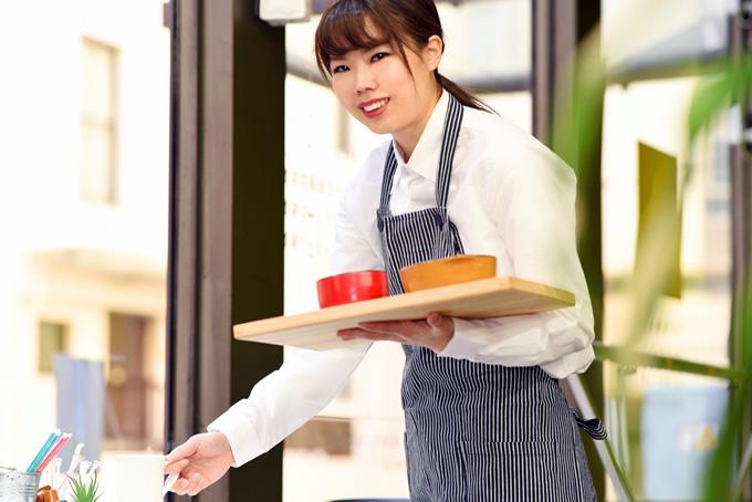 料理を運ぶアルバイト女性