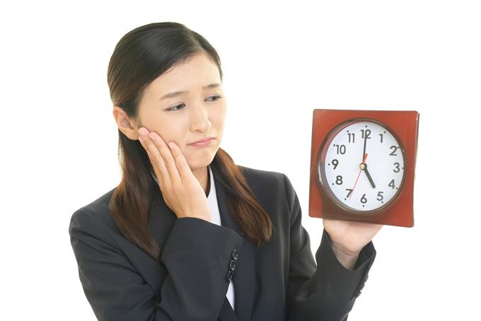 時計を持って悩む女性
