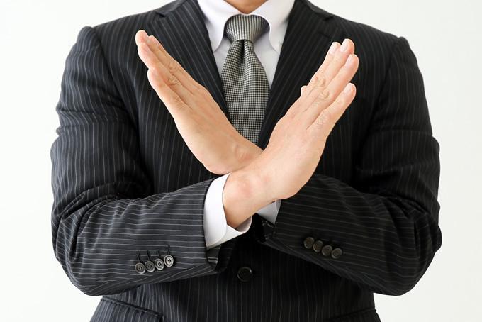 バツサインをするスーツを着た男性