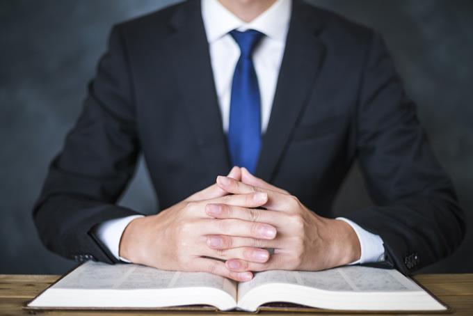 開いた本の上に手を置くビジネスマン