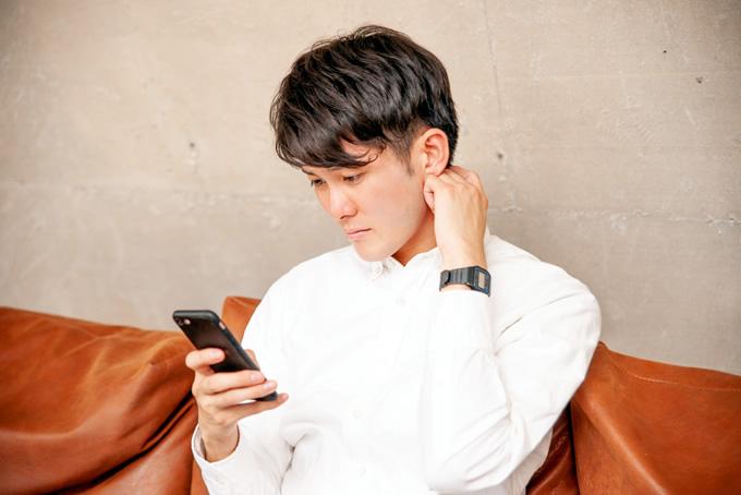 スマートフォンの着信記録を見る男性