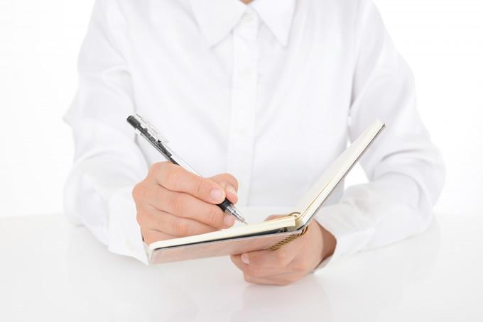 ノートに書く男性
