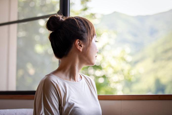 窓際でたたずむ女性