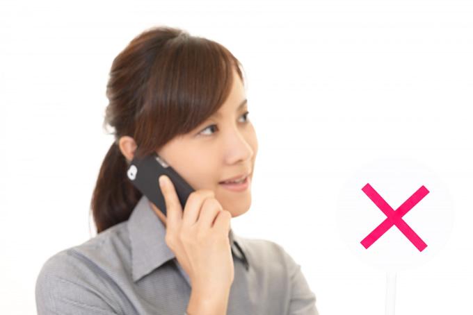 電話をしている女性にバツサイン