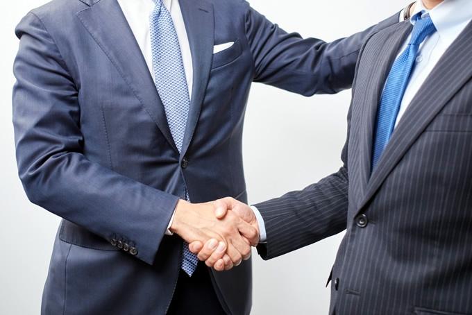 肩を叩いて握手をしている男性