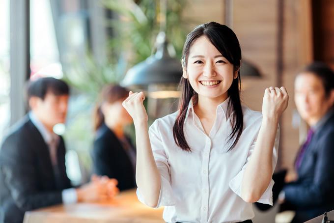 職場でガッツポーズする女性