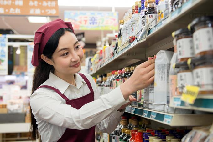 スーパーで品出しをする女性