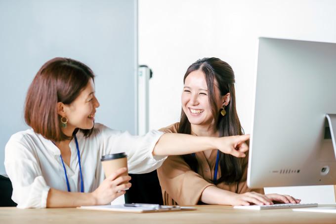 笑顔で新人に仕事を教える先輩
