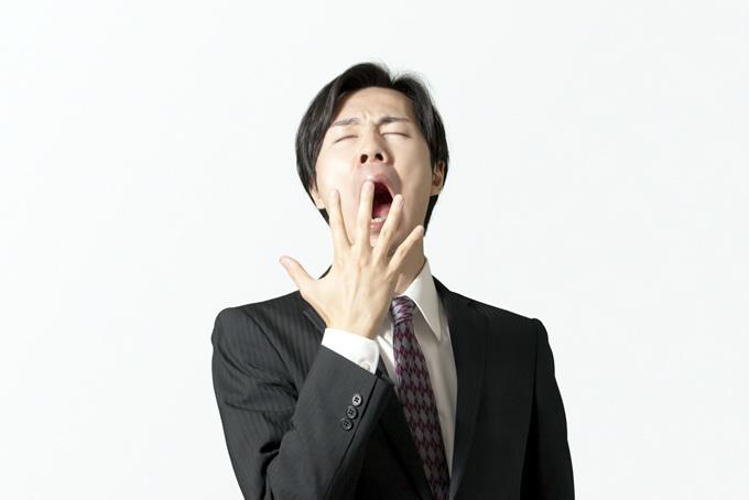 仕事中にあくびをする男性