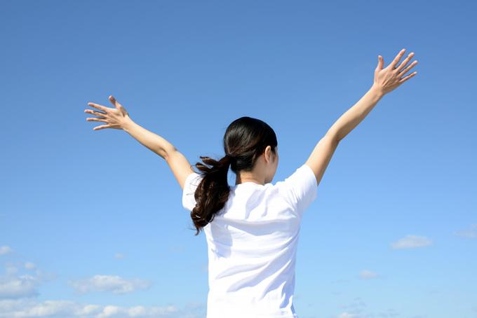 青空で手を広げる女性