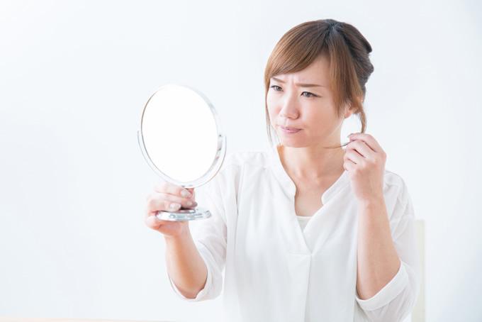 手鏡で髪型をチェックする女性