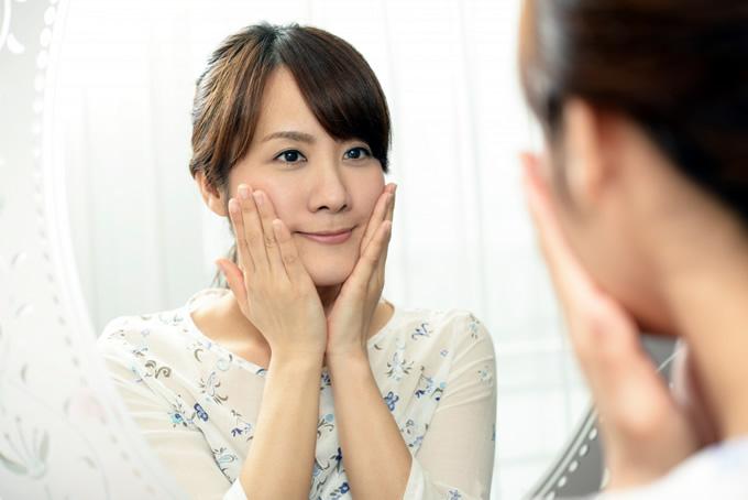 鏡でメイクを確認する女性