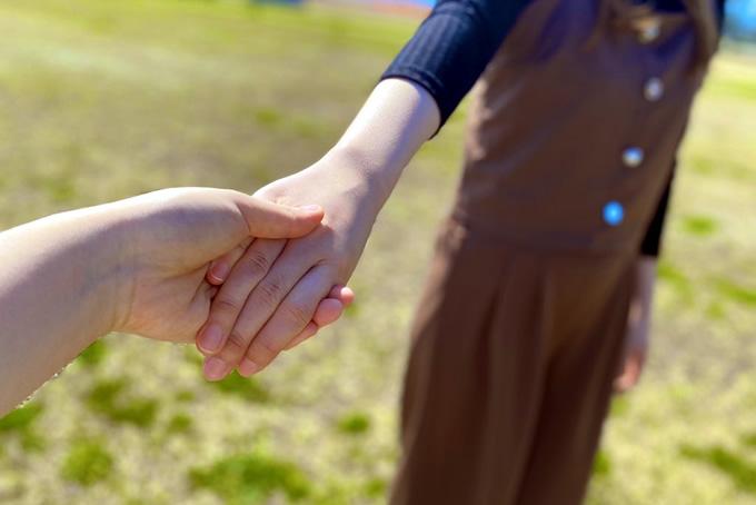 友達と手を繋ぐ女性