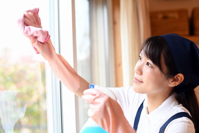 窓を拭き掃除する女性