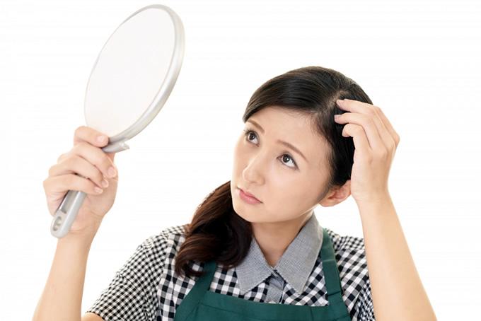 髪を鏡で確認する女性