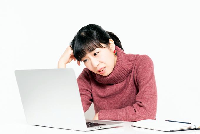 パソコンを見てショックを受ける女性