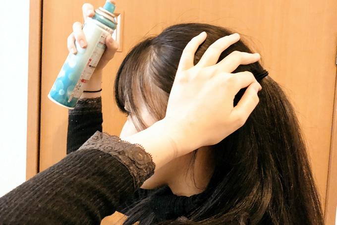 髪にスプレーしている女性
